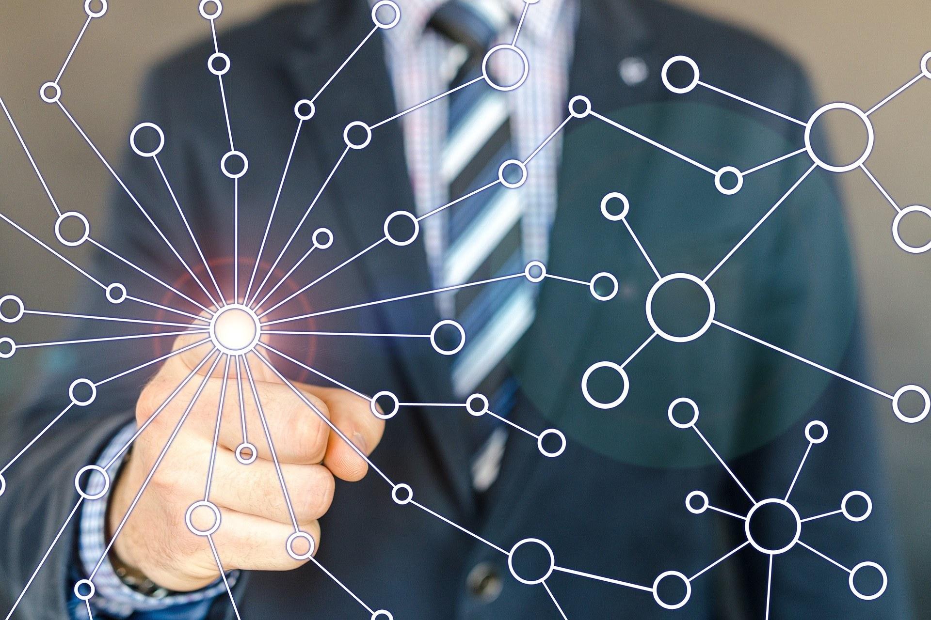 Mann i dress peker på et punkt i et illustrert nettverk